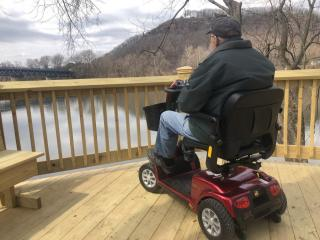 Man on wheelchair on park observation deck viewing the Connecticut River and Mt. Sugarloaf.