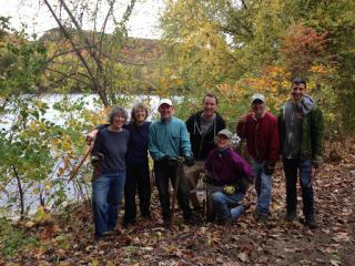 Seven people clearing river walk site with autumn foliage, river and mountain in background.
